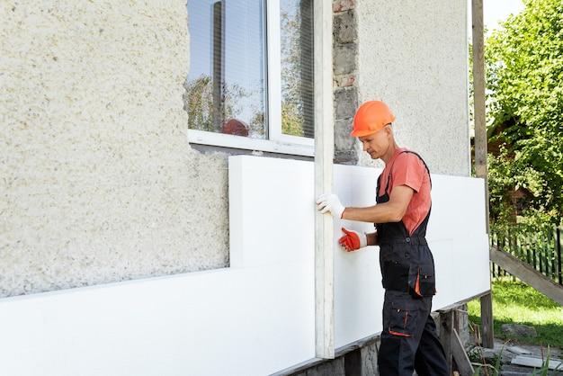 Ocieplenie domu pianką. pracownik sprawdza za pomocą aluminiowej linijki do tynku dokładność ułożenia płyty styropianowej na elewacji.