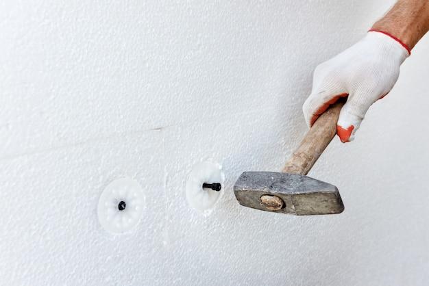 Ocieplenie domu pianką. pracownik używa młotka do kołków do mocowania płyt styropianowych.