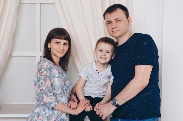 Ocieplenie i relaks. matka, ojciec i syn przytulanie. pojęcie rodziny, macierzyństwo, wnętrze, dom, dzieciństwo, dzień matki, dzień dziecka