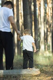 Ocieplenie serca obejmuje małego syna i jego ojca w ciepłych promieniach słońca