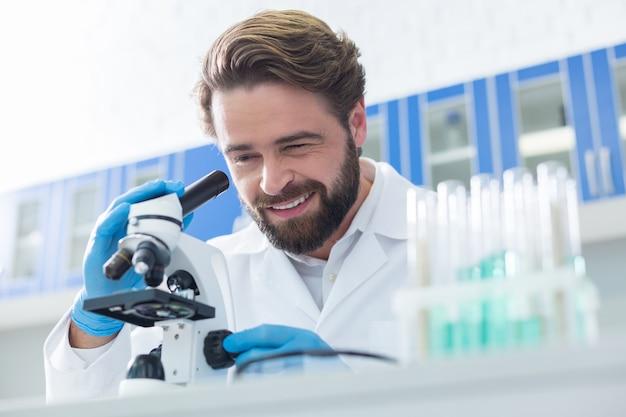 Oczekiwane rezultaty. wesoły, inteligentny profesjonalny naukowiec patrzy przez mikroskop i uśmiecha się, patrząc na wyniki swoich badań