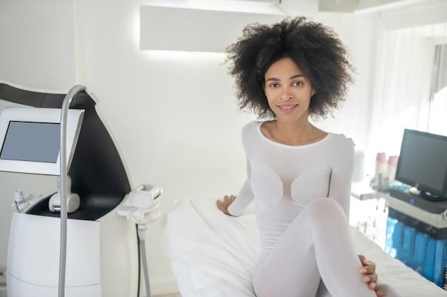 Oczekiwanie. młoda radosna kobieta w specjalnych białych ubraniach siedzi w salonie piękności podczas oczekiwania