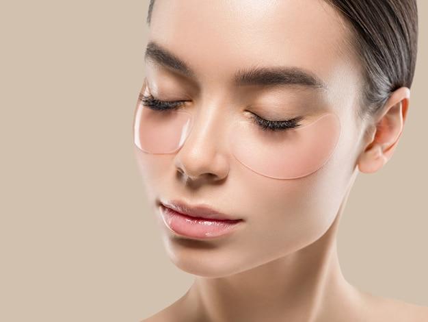 Oczy maska azjatyckie kobiety twarz kosmetyczna. kolor tła. brązowy.