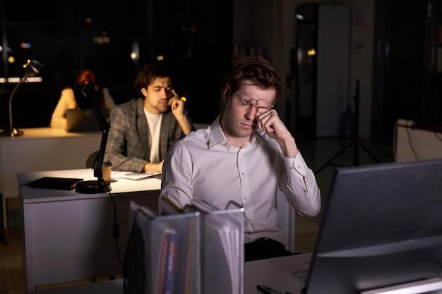 Oczy młodego męskiego pracownika biurowego bolą od przemęczenia, pracując na komputerze, w biurze w nocy ze współpracownikami, kaukaski facet w stroju wizytowym jest zmęczony, ma kłopoty w pracy. widok z boku
