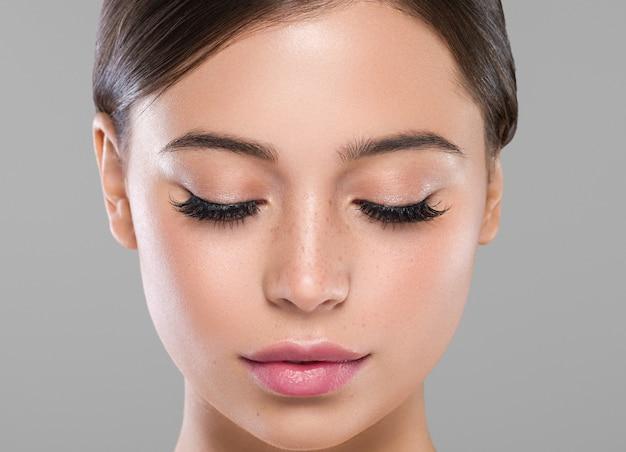 Oczy rzęsy twarz kobiety z bliska naturalny makijaż zdrowej skóry. strzał studio. kolor tła.