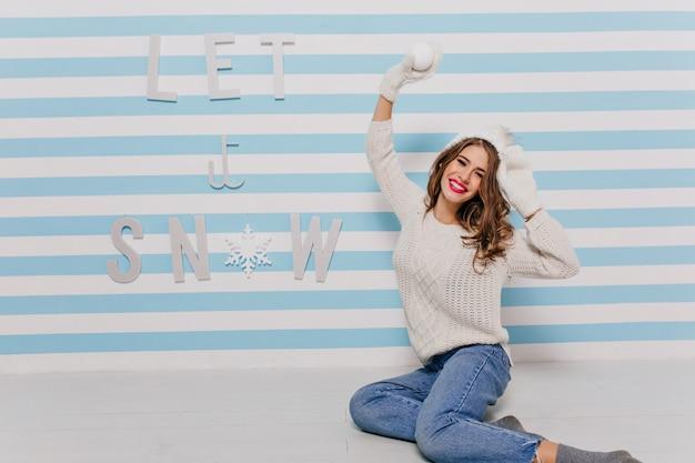 Oczy ślicznej dziewczyny lśnią radością w oczekiwaniu na zabawną grę w śnieżki. zdjęcie modelu w dżinsach na ścianie w paski