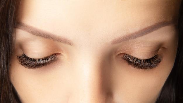 Oczy z pięknym długie rzęsy zbliżenie. przedłużanie rzęs w kolorze brązowym, objętość 3d lub 4d. pielęgnacja rzęs, laminowanie, przedłużanie, farbowanie, zwijanie