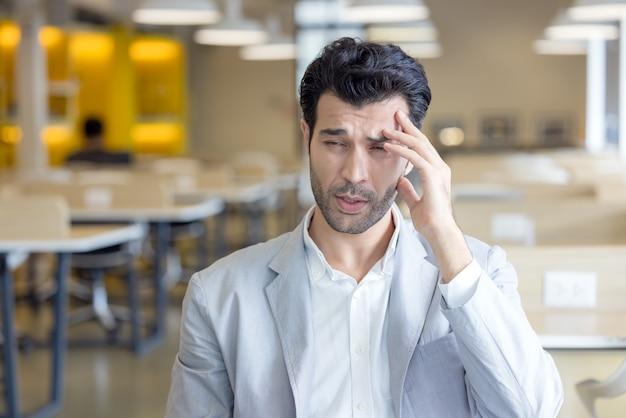 Oczy zmęczonego młodego mężczyzny są zmęczone pracą przy komputerze, a zestresowany mężczyzna cierpi na ból głowy i słabe widzenie. korzystaj z laptopa, siedząc przy nietypowym stole.