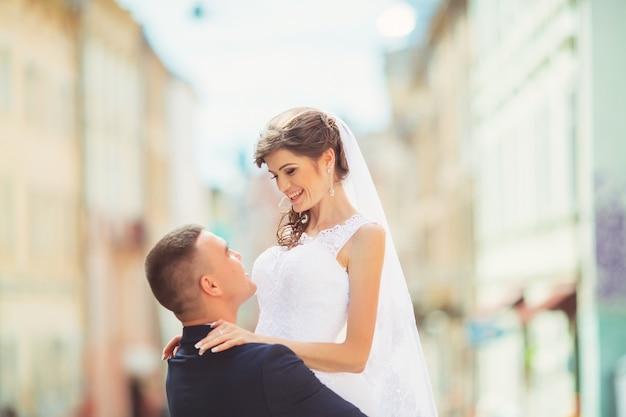 Oczyść delikatną, pochyloną pannę młodą, trzymając ją w ramionach i namiętnie całując, zdjęcie ślubne w słoneczny dzień na tle ścian w kolorze piasku. świeżo poślubiona para tańczy w parku, tango uliczne.