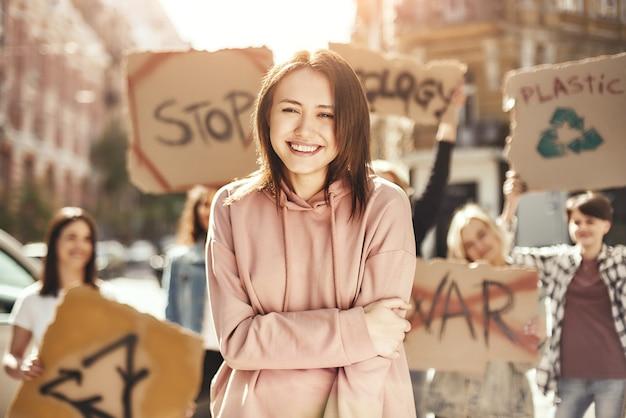 Oczyść swoją planetę szczęśliwa młoda kobieta trzymająca skrzyżowane ręce i protestująca na rzecz ekologii z grupą