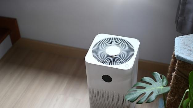 Oczyszczacz powietrza w komfortowym salonie z rośliną domową na drewnianej podłodze.