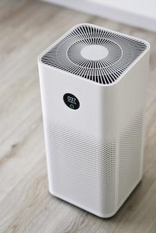 Oczyszczacz powietrza w pomieszczeniu z cyfrowym monitorem w sypialni, który pokazuje jakość powietrza w pomieszczeniu i poziom zanieczyszczenia powietrza w pomieszczeniu pm 25 to poważny problem zdrowotny dotyczący środowiska, który dotyka wszystkich