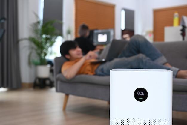 Oczyszczacz powietrza w salonie i młody człowiek na kanapie.