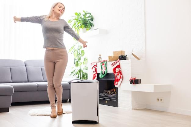 Oczyszczacz powietrza w salonie, kobieta pracująca z laptopem z filtrem do pomieszczenia czystego
