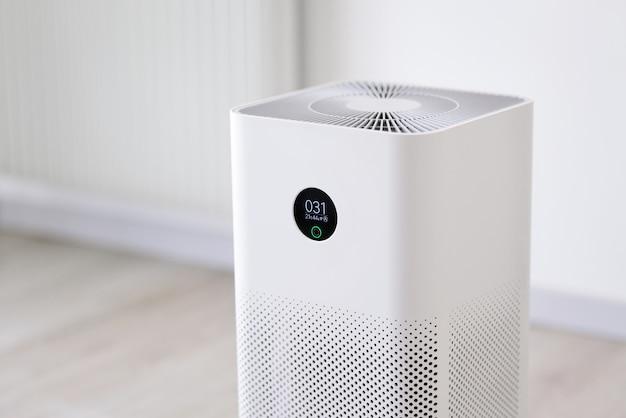 Oczyszczacz powietrza w salonieoczyszczacz powietrza usuwający drobny kurz w domuprotect koncepcja pyłu i zanieczyszczenia powietrza pm 25zbliżenie wewnętrznego oczyszczacza powietrza z ekranem monitora, który pokazuje jakość powietrza w pomieszczeniu