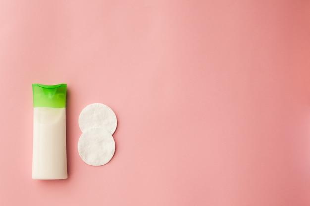 Oczyszczający krem do twarzy i wacikiem z odżywką. różowe tło. usuwanie makijażu.