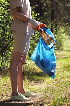 Oczyszczanie lasu z plastikowych odpadów nienadających się do recyklingu. młoda dziewczyna w rękawiczkach zbiera śmieci do worka. ratowanie środowiska przed katastrofą ekologiczną. wolontariusze, koncepcja eko-aktywistów.