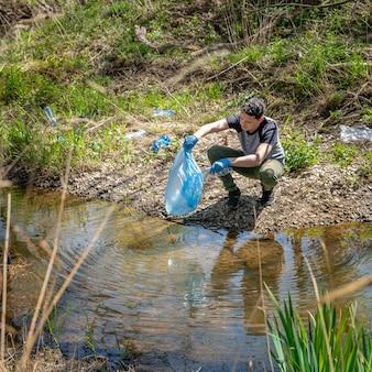 Oczyszczanie odpadów z tworzyw sztucznych na brzegu rzeki przez wolontariusza. pomaganie przyrodzie i ochrona środowiska
