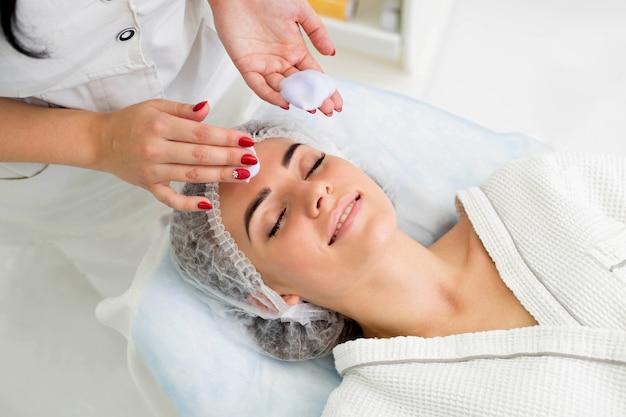 Oczyszczanie skóry pianką, piękna kobieta w gabinecie kosmetycznym urody. praca kosmetologa.