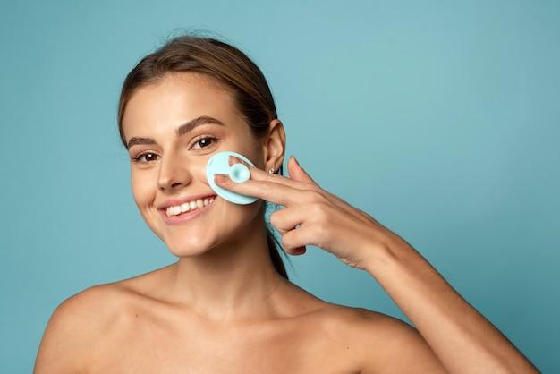 Oczyszczanie skóry silikonową szczoteczką do mycia. urocza młoda kobieta zmywa makijaż na niebieskim tle