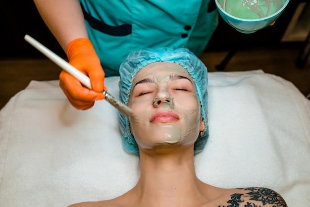 Oczyszczanie twarzy, kosmetologia, maseczka upiększająca, uśmiechnięta kobieta, spa