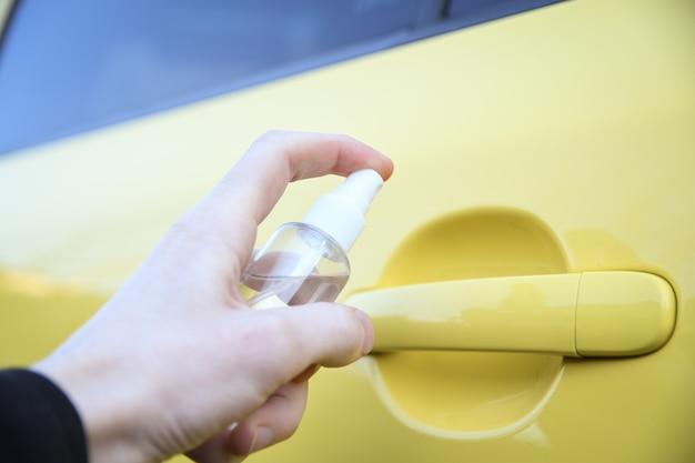 Oczyszczanie wnętrza samochodu i spryskiwanie płynem dezynfekującym. dezynfekcja kierownicy i klamek samochodu. koronawirus, ochrona covid-19 dezynfekcja wnętrza pojazdu
