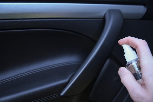 Oczyszczanie wnętrza samochodu i spryskiwanie płynem dezynfekującym. dezynfekcja kierownicy i klamek samochodu. koronawirus ochrona. ochrona przed wirusami dezynfekcja wnętrza pojazdu