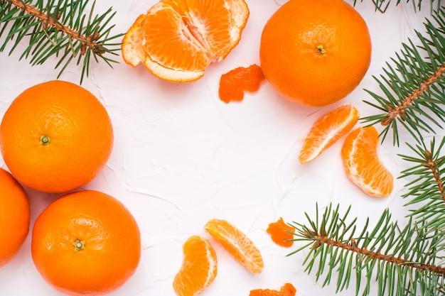 Oczyszczone plastry mandarynki, całe mandarynki i gałęzie jodły na białym stole, widok z góry
