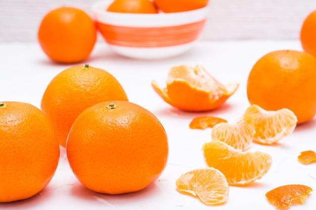 Oczyszczone plastry mandarynki i całe mandarynki na białym stole