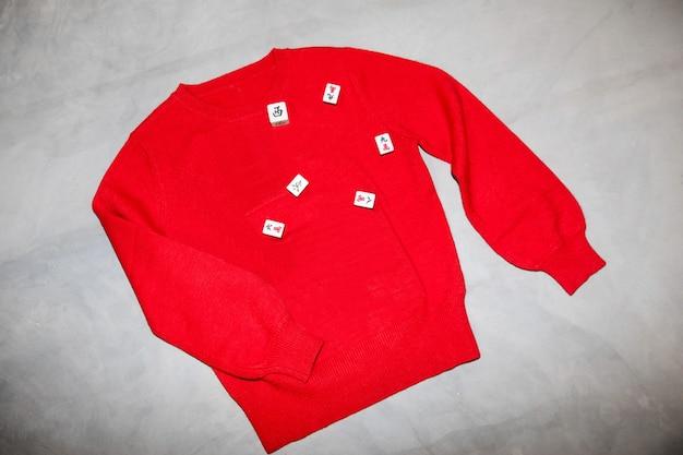 Od góry dzianinowy ciepły sweter w kolorze czerwonym oraz kostki ułożone na szarym stole