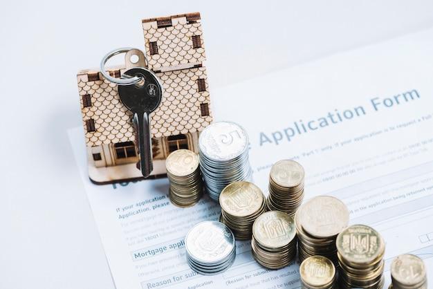 Od góry monety i klucz do wniosku o kredyt hipoteczny