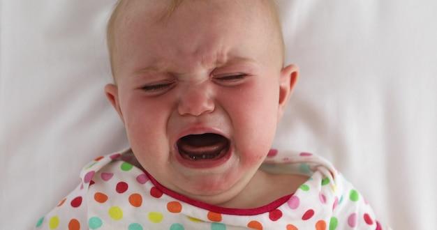 Od góry słodkie niemowlę w kolorowej odzieży płaczącej podczas leżenia na białym prześcieradle