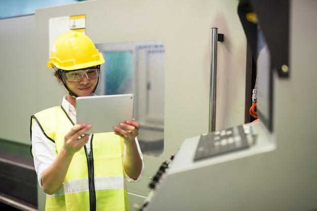Od pasa do góry azjatycka pracownica fabryki używa tabletu do programowania wybierania i umieszczania maszyn elektronicznych do linii montażowej do montażu powierzchniowego płytek drukowanych. przemysł mikroprocesorowy.