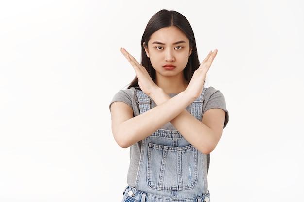 Od pasa do góry poważnie wyglądająca pewna siebie zdeterminowana azjatycka brunetka żądająca zatrzymania pokaż krzyż ręce marszcząc brwi dąsając ostrzegaj daj silną odmowę odrzucenie ohydna oferta zakazująca tabu biała ściana