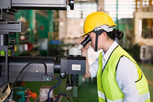 Od pasa do góry pracownica z kaskiem patrzy na mikroskop, aby sprawdzić kontrolę jakości wydajności szkła w fabryce produkcyjnej. przemysł produkcyjny do produkcji z zapewnieniem jakości qa lub qc.