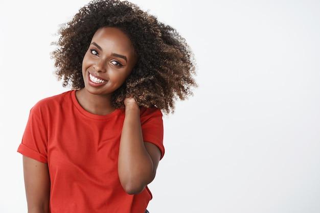 Od pasa do góry ujęcie delikatnej i romantycznej pięknej afroamerykańskiej kobiety z fryzurą afro trzymającą rękę za szyją i uśmiechającą się nieśmiało, rumieniąc się, zalotnie pozuje na białej ścianie w czerwonej koszulce
