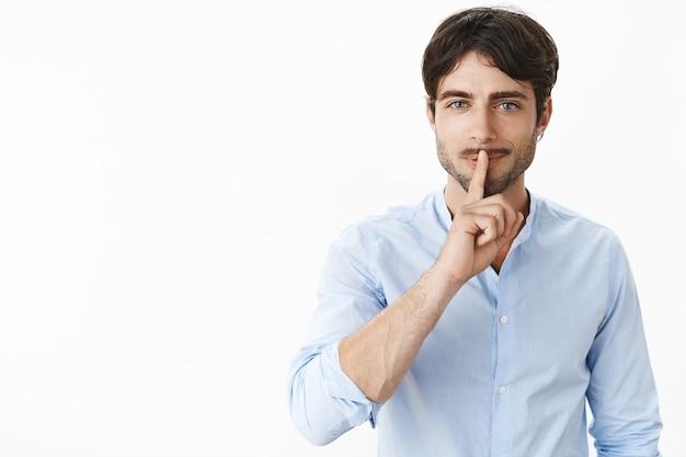 Od pasa do góry ujęcie seksownego przystojnego mężczyzny sukcesu z brodą i niebieskimi oczami, uśmiechający się niegrzecznie, wykonujący cichy gest nad złożonymi ustami, prosząc o zachowanie głosu jako przygotowującego sekretną niespodziankę nad szarą ścianą