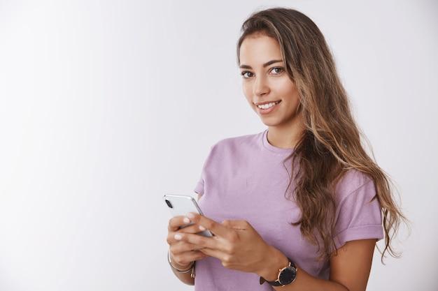 Od pasa do góry wspaniała uśmiechnięta szczęśliwa dziewczyna trzymająca smartfona patrząca zachwycona delikatna kamera, myśląca o uchwyceniu pod selfie publikującym zdjęcie w sieci społecznościowej, prosząc o zrobienie zdjęcia biała ściana