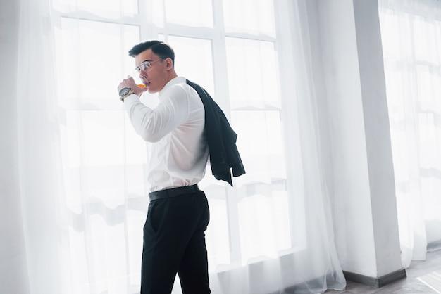 Od tyłu. luksusowo wyglądający mężczyzna w klasycznym stroju stoi w pokoju i trzyma górę garnituru i szklankę z alkoholem.