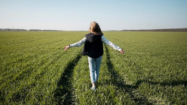 Od tyłu strzał młodej dziewczyny w polu