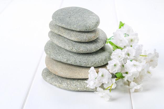 Od zdroju kamieni robić równowaga ostrosłupom na białym drewnianym tle.