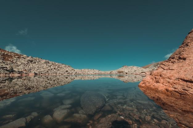 Odbicia jeziora polodowcowego w górach w sezonie jesiennym