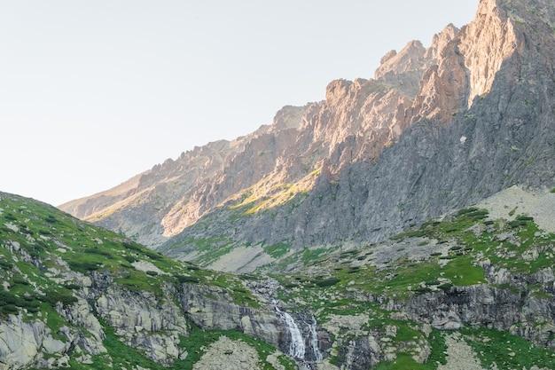 Odbicia w spokojnej wodzie jeziora, wodospadzie i górach o zachodzie słońca.