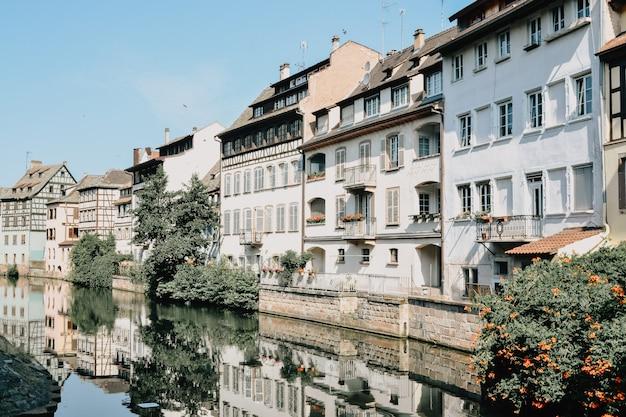 Odbicie białych domów z brązowymi dachami otoczonych zielonymi roślinami w wodzie