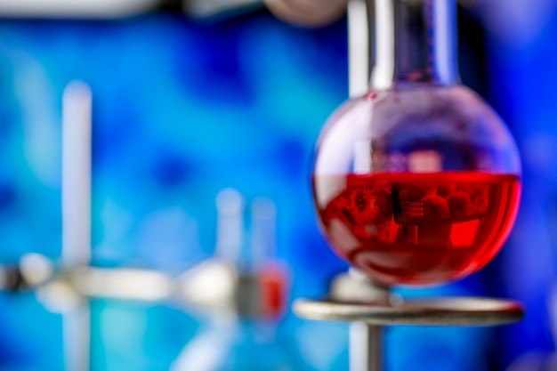 Odbicie drobnoustroju z ekranu komputera w czerwonym roztworze odczynnika w szklanej kolbie chemicznej do eksperymentu naukowego w celu zdiagnozowania patogennego mikroorganizmu lub wirusa.