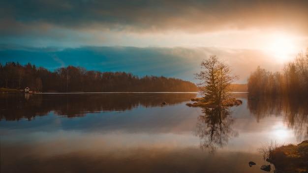 Odbicie drzew w jeziorze pod niesamowitym kolorowym niebem uchwyconym w szwecji