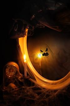 Odbicie ducha w lustrze na stole ze świecą, zegarem, spowitym pajęczynami