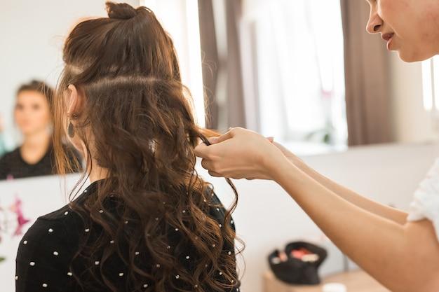 Odbicie fryzjera robi fryzurę dla kobiety w fryzjera. pojęcie mody i urody