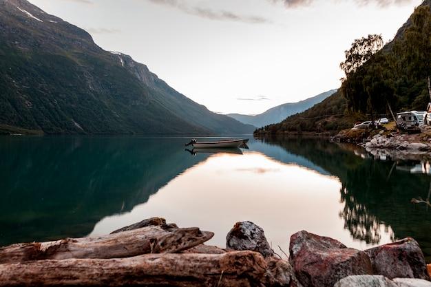 Odbicie góry i łodzi na spokojne jezioro
