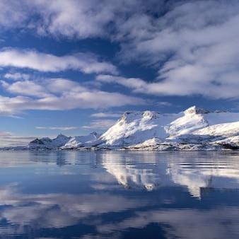 Odbicie klifu pokryte śniegiem w wodzie pod pięknymi chmurami na niebie w norwegii
